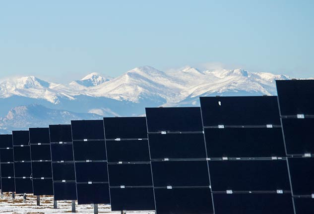 utility scale solar panels with snow covered mountains behind them