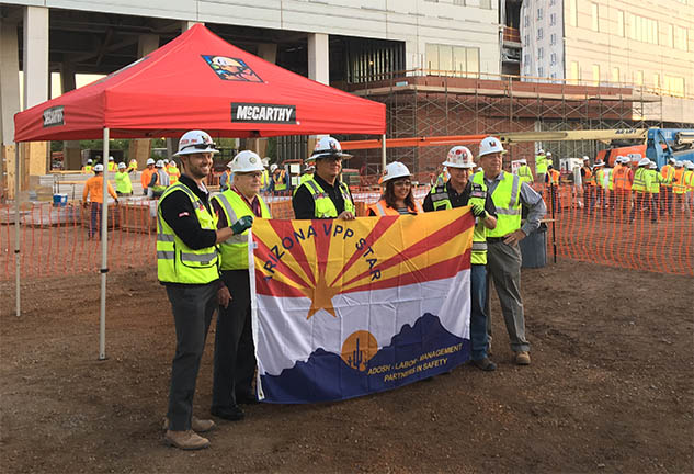 McCarthy Construction Workers Hold Banner Celebrating ADOSH Award