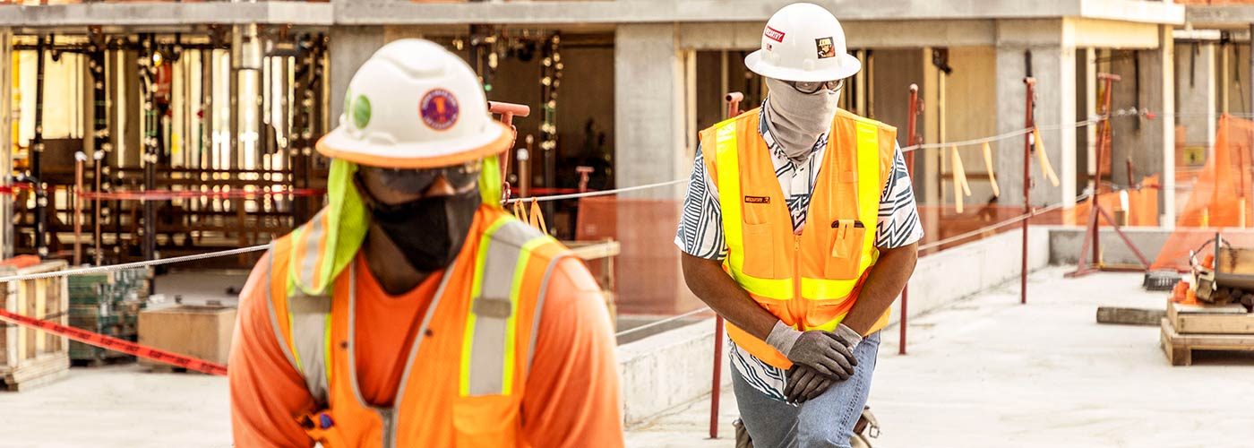 2 construction workers stretching