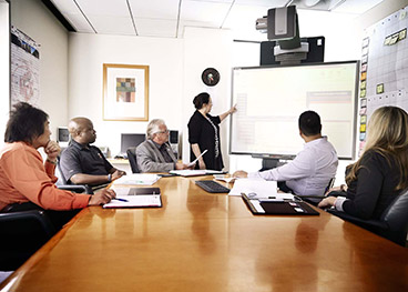Woman presenting to a group of mostly men in an office