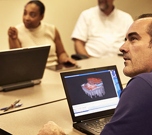 Group in a meeting including a man on a laptop