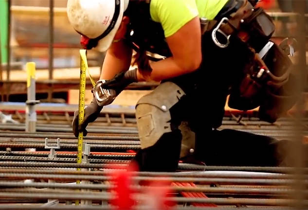 Construction worker measuring rods on site.