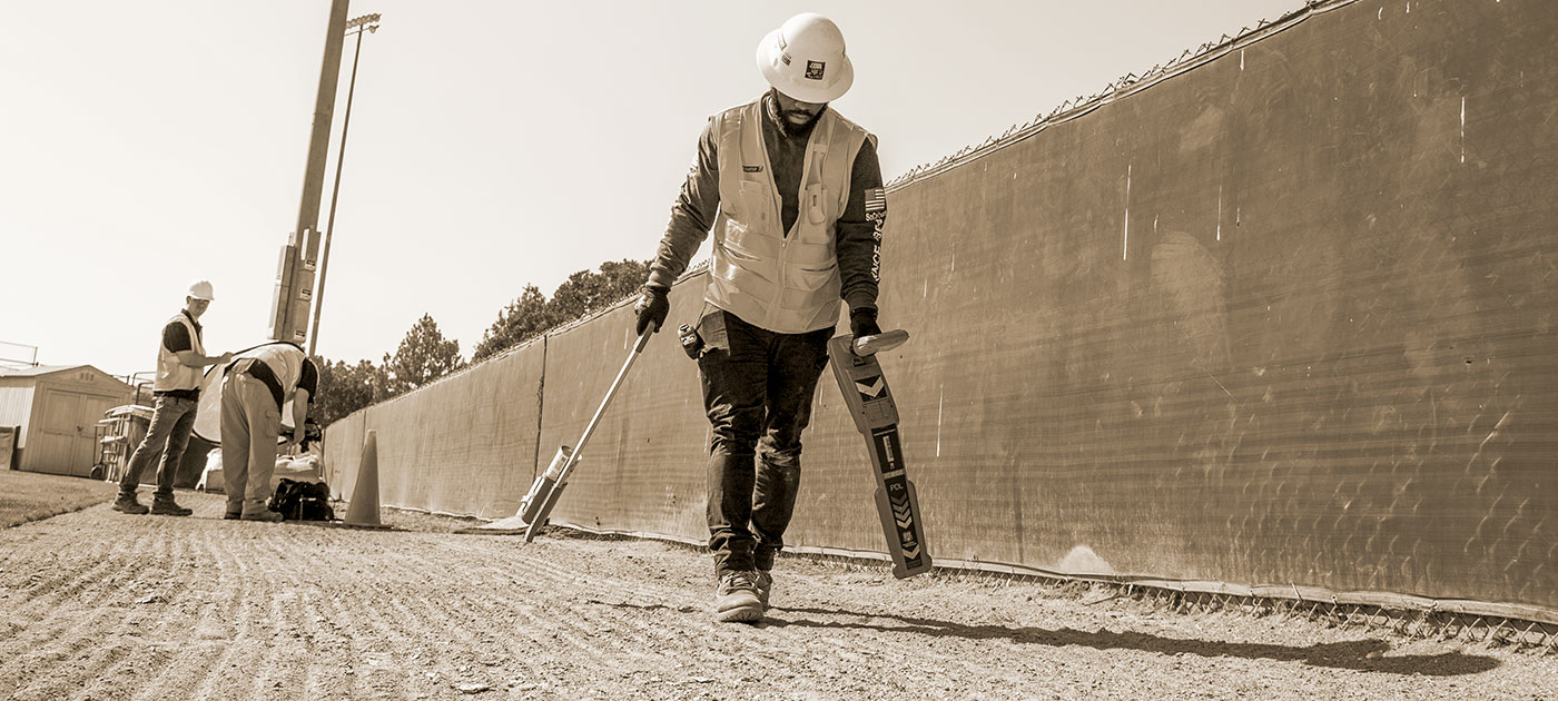 construction worker carrying mapping equipment