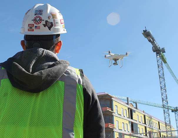 construction worker watching a drone