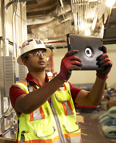 McCarthy intern looks at an iPad at a job site