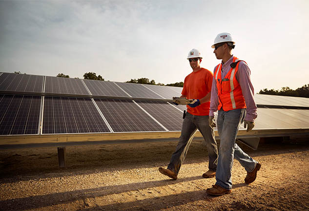 Two Construction Workers Walking in Front of Solar Panels