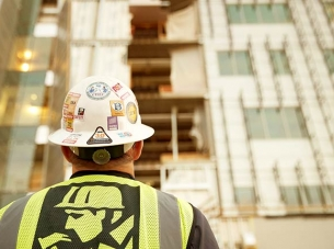 construction worker looks up at building