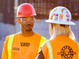 two construction workers talking to one another