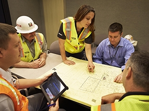 group of people sitting around table looking at plans
