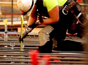 Construction worker measure rods on a work site.
