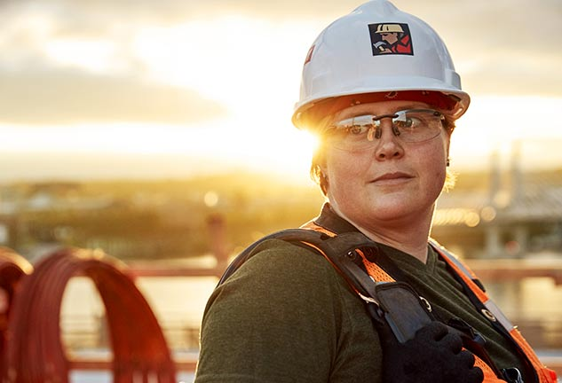 woman in hard hat with sun setting behind her