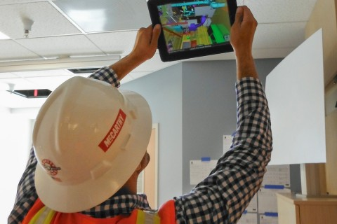 McCarthy construction worker looking at an image on an iPad